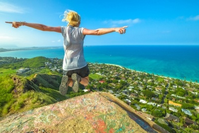 Woman jumping on a scenic overlook on Oahu