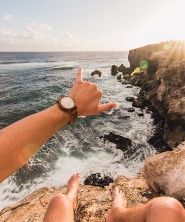 Man sitting on a cliff in Hawaii making the shaka sign