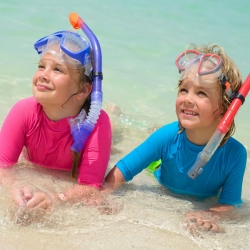 Two small children in the surf with snorkeling masks