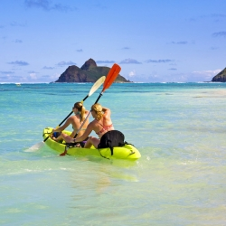Two people on a sea kayak in the waters off Oahu