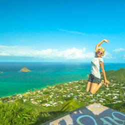 Woman jumping in the air during a hike on Oahu's Lanikai Pillbox