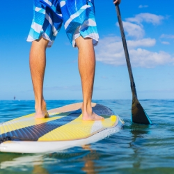 Man with blue shorts on a yellow paddleboard