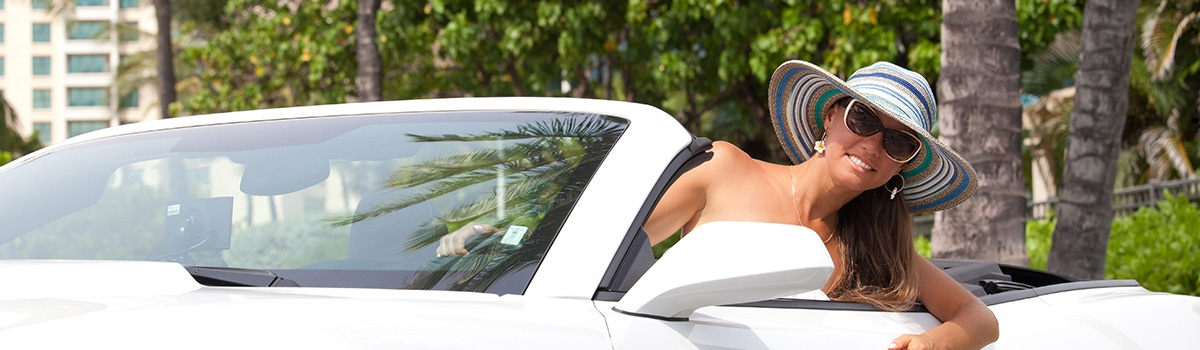 Woman with hat in white convertible on Oahu