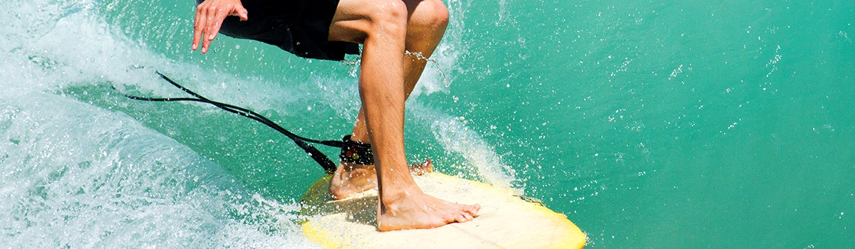 Male surfer with leg leashed to yellow board