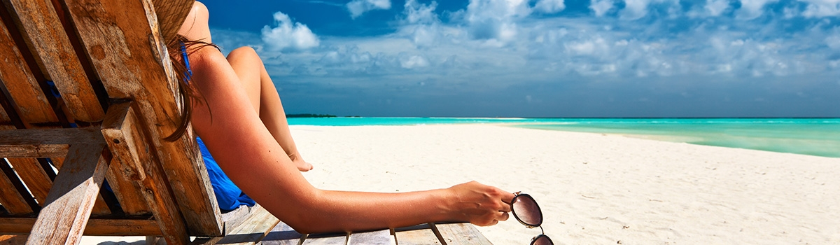 Woman holding sunglasses relaxing on an Oahu beach