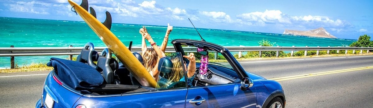 Women driving down the street by the ocean in a blue convertible