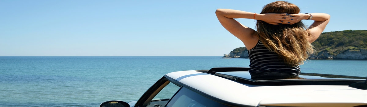 Woman looking at the ocean through a convertible car roof
