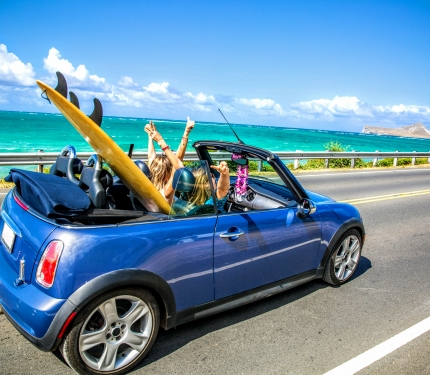 Girls in convertible driving along the beach