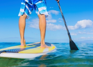 Man in  blue board shorts on a paddleboard