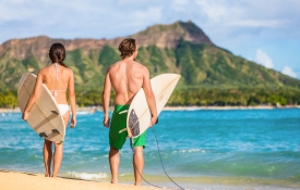 Couple with surfboards walking toward an Oahu beach