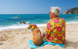 Senior man in Hawaiian shirt sitting on beach with dog