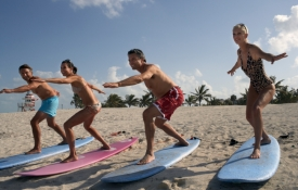 People taking a surfing lesson on a beach