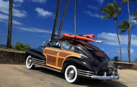 Wood paneled car with surfboard on roof