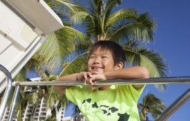 Young boy looking from a balcony in Hawaii