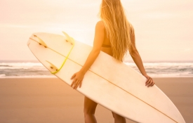 Blond woman holding surfboard and looking at the ocean