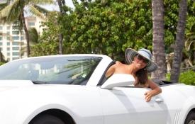 Woman with hat in white convertible