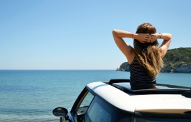 Woman looking at the ocean through the sunroof of a white car.