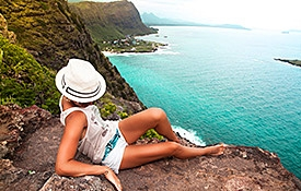Woman sitting on a cliff overlooking an Oahu beach