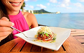 Woman eating at an outdoor Oahu restaurant