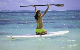 Woman sitting on a paddleboard at an Oahu beach