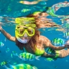 Beautiful girl snorkeling with fish