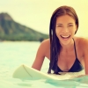 Smiling woman sitting on surfboard off Oahu